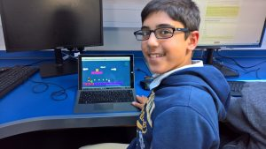 Student coding a platforming game in C# using Unity.